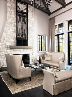 A towering coursed limestone fireplace accented by a 19th century iron door from Italy anchors the sitting area of this great room.   An antique rug, linen-covered custom-designed bench, a pair of Avrett tables and silk-covered high-backed sofas complete the space. Large picture windows allow for ample natural lighting and incredible views.