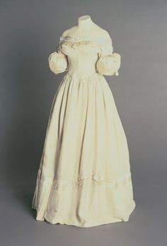 1830's Dress Cream, short puffed sleeves on arms. Wide neckline, gold satin ribbon trim. The Philadelphia Museum of Art