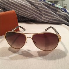 Tory Burch aviator sunglasses Gold trim Tory Burch aviator sunglasses. Brown, navy & white pattern on side of glasses with engraved gold logo. In great condition- only worn a few times. Comes with carrying pouch & orange Tory Burch sunglass case. Willing to negotiate price for reasonable offer. Tory Burch Accessories Sunglasses