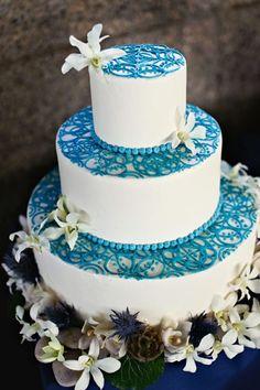 Torte mit blaue Deko und weißen Blumen verziert