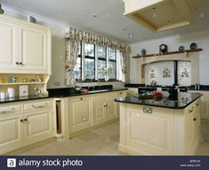 Download this stock image: Cream island unit with black granite worktop in large country kitchen - BPBTJN from Alamy's library of millions of high resolution stock photos, illustrations and vectors.