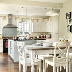 Family kitchen with off-white walls, wood flooring, white dining set and pendant lights