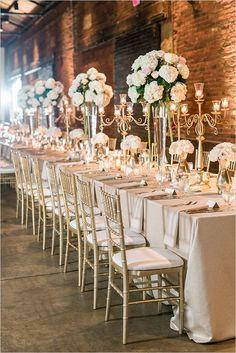 White Wedding centerpieces  Gold Reception Chairs  Exposed Brick Wedding Reception