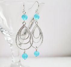 Elegant and sassy, these silver earrings will make you feel like Summer never ends!  Created with Matte silver plated Triple Hoop pendants and