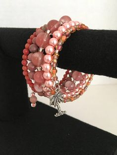 Reminisce about the sky views of a beach sunset with this OCEAN SUNSET wrapped bracelet made with stainless steel memory wire that is adorned with a palm tree charm! There is a coordinating bead at the opposite end. All beads are in the peach/orange/pink/red hues. The bracelet