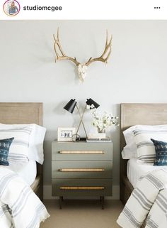 Gorgeous grey dresser between two beds and antlers above
