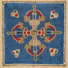 """the central motif is a """"double vajra,"""" said to represent a double thunderbolt, an important symbol in Tibetan Buddhism."""