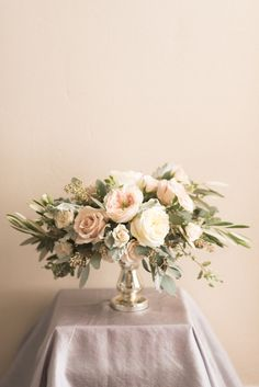 Emlily Floral | Blush centerpiece with olive and eucalyptus foliage on silver mercury glass.