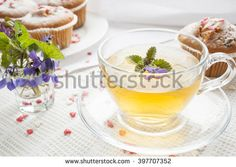 Cup of green tea with lemon balm and tasty muffins with sugar hearts, blue spring flowers viola on light background