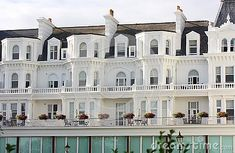 An exterior of a white painted seaside building and it`s balconies in Eastbourne in East Sussex England.