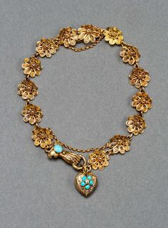 Turquoise Gold Filigree Bracelet 19th Century. Designed as fourteen filigree links in the form of gold rosettes terminating in a jeweled gold hand suspending a turquoise and ruby gold heart, the reverse with a glazed panel, fitted with two integral clasps and safety chains. In original fitted leather box. Georgian or Victorian, early to mid 19th century, English. 7 ½ in. (19 cm.) long; the heart-1/2 in. (1.3 cm.) long