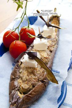 Un antipasto (o secondo piatto) molto scenografico e goloso, nella sua semplicità. Melanzane ripiene con salsiccia, cubetti di robiola e pomodorini confit.