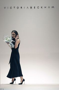 VB She's in fashion: Victoria accepted a bunch of flowers as she hit the catwalk at the close of the show in an elegant black dress and super high heels