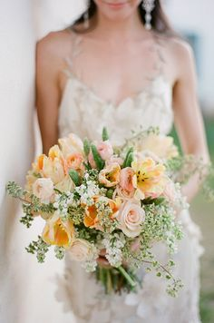 Peach colored roses, tulips and ranunculus come together for a beautiful rustic chic wedding bouquet.