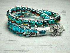This wrap around leather bracelet is perfect to wear in the Spring time, with it's bright blue green beads and white leather cording will add that dash of color to any outfit.