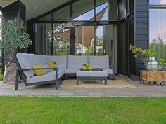 Super strakke hoek loungeset voor een moderne tuin. Deze loungebank is van aluminium en heeft een donker grijs frame met licht grijze kussens. Op het terras staat een olijfboom en een houten bijzet tafeltje. Er zijn gele accessoires gebruik die mooi passen bij de gele bloemen | Tuininspiratie Metal Sofa, Outdoor Furniture, Outdoor Decor, Wood And Metal, Aluminium, Charcoal, Patio, Home Decor, Products