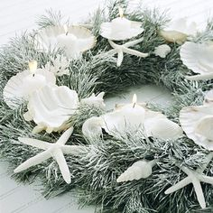 Seasonal Glow Wreath  Shells hold votives on a lightly flocked coffee table wreath accented with starfish and coral. To turn the display into a fancy centerpiece, add a hurricane or a pillar candle to the center. Never leave a burning candle unattended.