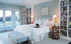 Love the blue and white--very peaceful for the bedroom. Bookcases are wonderful. Ottoman at foot is perfect. Wall light fixtures--good idea.
