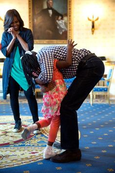 The First Lady watches as President Obama gives a hug to a little girl in the White House. the President is bent down to reach the small child.