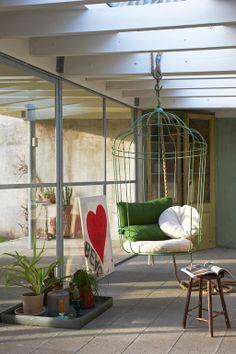 Groepeer je planten op een tafel of een kastje, of zet je planten bij elkaar op een dienblad. Heb je mooie stevige balken in je kamer, die wel wat kunnen hebben/dragen? Hang dan een mooie hangstoel op. Hier is gekozen voor een ijzeren exemplaar van Sukha.   The hanging chair is from 'ontwerpduo' http://www.ontwerpduo.nl/ in Eindhoven and sold by the store SUKHA in Amsterdam: http://www.sukha-amsterdam.nl/interieur/