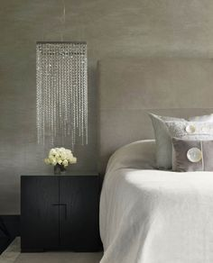 I really love the placement of this bedside light (by Kelly Hoppen) and the juxtaposition it  creates against the concrete style wall. The bunch of short steam roses and pillows just set it all off. Stunning.