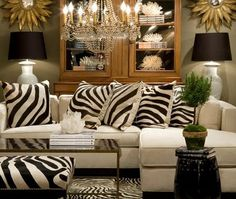 gold sunburst mirrors, chandelier, tall hutch, matching lamps, white sofa with chaise, ZEBRA!