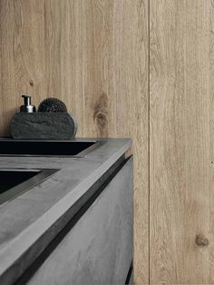 La cuisine Cloe Vip mêle la finesse des lignes à des matériaux tout autant innovants que nobles. A l'unisson, les deux matériaux créent une empreinte minérale et végétale. Le plan de travail et les façades des meubles bas s'habillent d'éco-ciment foncé d'une épaisseur de 2 cm. Tandis que les modules hauts, armoires et étagères laissent carte blanche au chêne de 6mm, au veinage tramé de nœuds.  ©Cesar