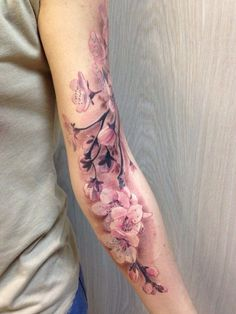Realistic pale pink cherry blossom tattoo on arm