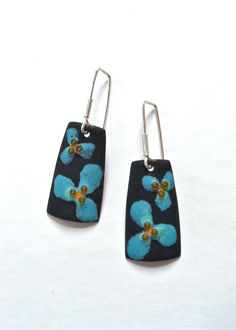 """Two simple blue flowers, with a dot of orange and three beads in the center. Lovely, simple, and fun - enough said!  These enameled earrings have my signature velvety, matte surface quality. The sterling silver earring wires are handmade in the studio. These measure 1-7/8"""" long from the top of the hook, and are 5/8"""" at the widest point.  [share title=""""love it, share it"""" socials=""""facebook, twitter, pinterest, google, bookmark""""]"""