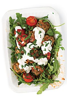 Lamb meatballs are simmered in a harissa-spiked tomato sauce, served over peppery arugula, and drizzled with bright yogurt-thickened aïoli.