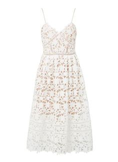 Polyester/Lace Broderie Sweetheart Dress. Neat fitting silhouette features a fitted splice panelled bodice with rouleaux straps and sweet heart neckline, complete with a full flare skirt in an all over Broderie lace and contrasting underlay. Available in White as shown.