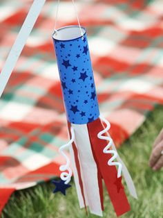 4th of July Wind chime  glue scrapbooking paper around a clean frozen juice-concentrate container, then extending paper a few inches beyond the can. Twist white chenille stems around a pencil for a curly shape, then tape them to the inside bottom edges of the wind sock. Add streamers in the same way.  Inside the top, tape two equal-length pieces of fishing line across from each other so the wind sock is balanced; tie together at the top for easy hanging