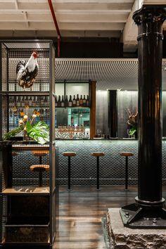 estanterias de reja con gallina y elementos decorativos zona de bar y cocina de restaurante y columna sobre base de cemento