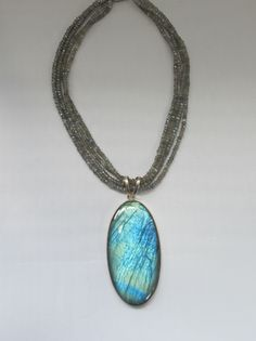 A dramatic style piece -- Four strands of faceted Labradorite gemstone beads adorned with a stunning highly chatoyant 3-inch long oval Labradorite pendant, bezel-set in 925-hallmarked sterling silver.