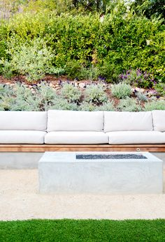 Wooden benches with grey cushions and outdoor grey fireplace