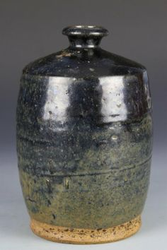 Chinese Black Glaze Vase, Jin period, black glazed wine jar with green hue along base, tall cylindrical body with small top opening. Height 9 in., Width 6 in.