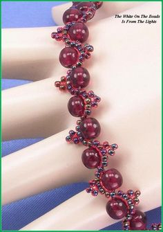 "Jewelry is made with small beads.Some are glass or stone. Adult supervision is recommended. This bracelet is made with Miyuki 11/0 garnet lined ruby glass seed beads along with 6mm garnet glass beads and hooks with a trailer hitch or snap clasp. Measures approx. 7 11/16"" long (including clasp) by 1/2"" wide and is a design pattern from: Korean Design. Priced at only $24.75 with ""FREE SHIPPING"""