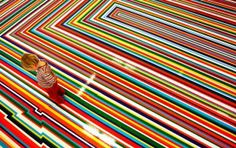 Esme Grant walks over 'ZOBOP 1999', a large scale installation by artist Jim Lambie. Photo by David Moir/Reuters