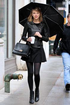 Taylor swift usando una falda y chaqueta de piel mientras camina bajo la lluvia