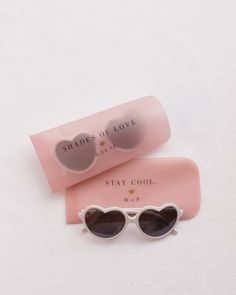 Heart-shaped sunglasses favors in vellum sleeves double as fun photo booth accessories