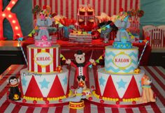 Twins Circus Carnival birthday cake with fondant elephants, lion, monkey, seal, and ringmaster bear.