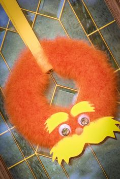 Lorax wreath: Orange feather boas wrapped around a styrofoam wreath, with a felt mustache and eyebrows, a pom pom nose and large googly eyes.
