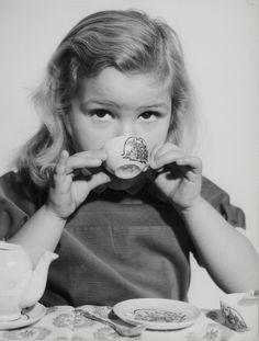 Kinderen, spelen, meisjes. Poppenmoedertje srinkt een kopje thee uit kopje van poppenserviesje. Nederland, 1950-1960.