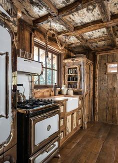 Perfectly rustic and charming cabin kitchen with exposed wood beams in the ceiling, reclaimed wood around the door frame on the edges of the cabinets, built-in breadbox, pendant light hanging from a vintage rope, and sweet antique stove and oven to complete the look.