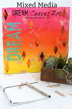 Try something new and create a Mixed Media Dream Canvas with DecoArt Misters, acrylic paint, gold leaf and metallic stickers.