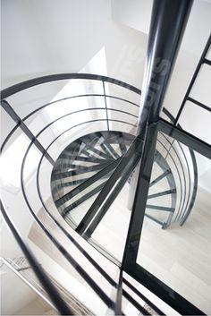 Photo DH82 - SPIR'DÉCO® Dalle de Verre. Escalier intérieur design en acier et verre pour une décoration contemporaine toute en transparence. Marches mécano-soudées avec dalles de verre clair feuilleté. Limon en tôle roulée soulignant les courbes de l'escalier en colimaçon. Rampe contemporaine avec main courante en tube débillardé et ergonomique, 3 lisses parallèles en fer rond parallèles. Finition : peinture. - © Photo : Nicolas GRANDMAISON
