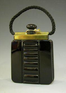 Flacon Ouvrez-moi, Lubin   Petit flacon en verre teinté noir, représentant un sac à main avec une anse en cordon tressé de satin. Une face est décorée en centre de cannelure montant du sac en métal doré. Bouchon noir elliptique. Petit cordon doré torsadé autour du col. 1936 / 1937