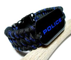 Paracord survival bracelet for law enforcement police officer. The bracelet has a high quality black dog tag with POLICE in blue. The wide bracelet has been done in the ladder rack weave, or trilobite