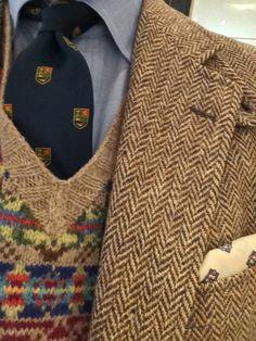 Light brown tweed jacket, light blue shirt, navy tie, tan fair isle vest