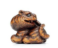 A Wood Netsuke Signed Minko, Edo Period (18th century) A striking model of a tiger, eyes inlaid in cowhorn 4.5cm. wide